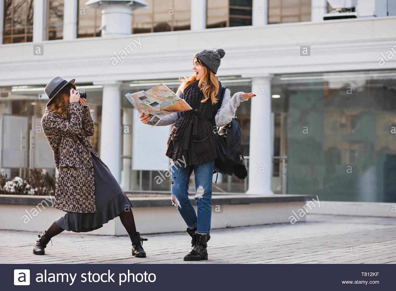 Momenti felici di divertenti turisti nella giornata di sole in una grande città. Funny gioiosa le ragazze che viaggiano insieme, divertendosi, rendendo foto, esprimere la vera brightful emozioni positive, elegante, migliori amici Immagini Stock