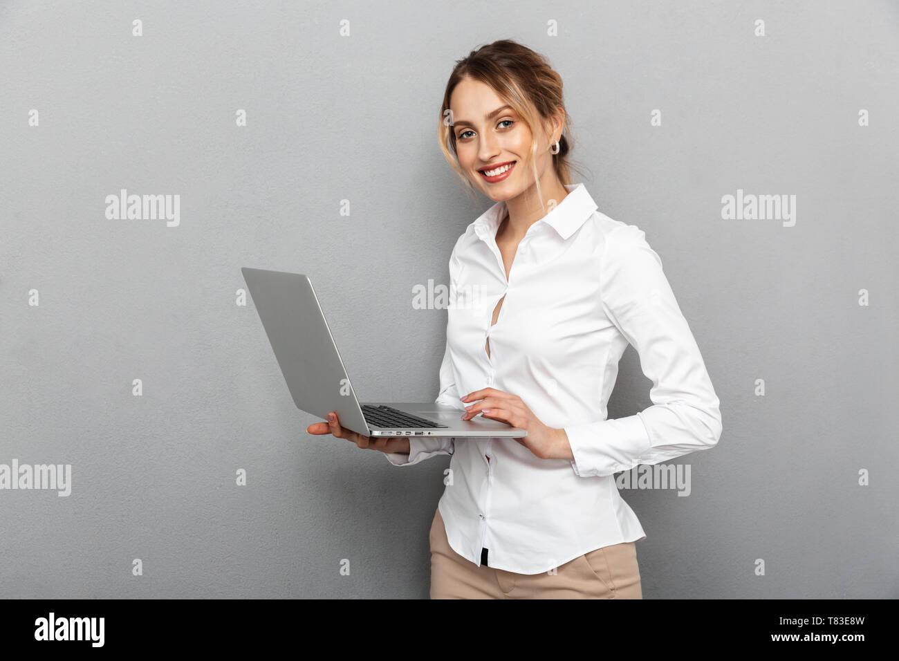 Foto di smart donna in abbigliamento formale e permanente tenendo portatile in ufficio isolate su uno sfondo grigio Immagini Stock