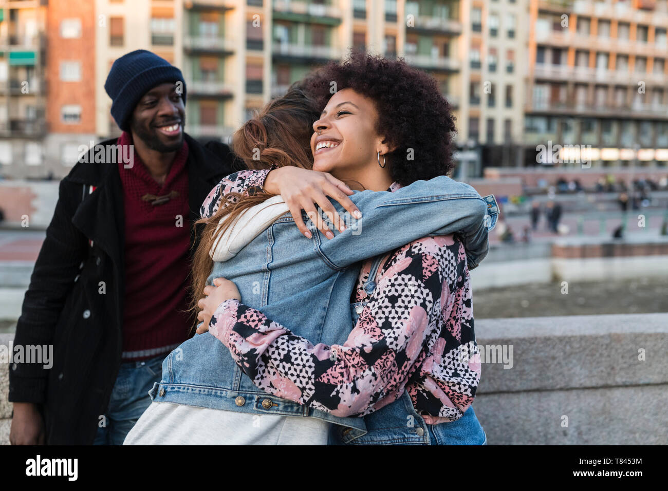 Due giovani donne abbracciando in strada di città Foto Stock