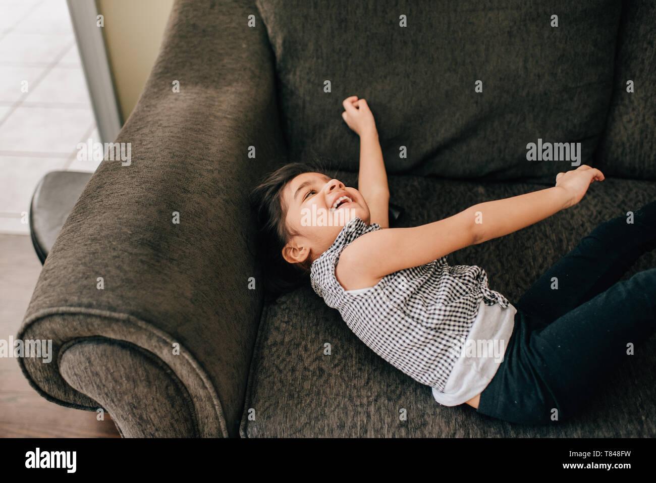 Ragazza distesa sulla poltrona di ridere Foto Stock