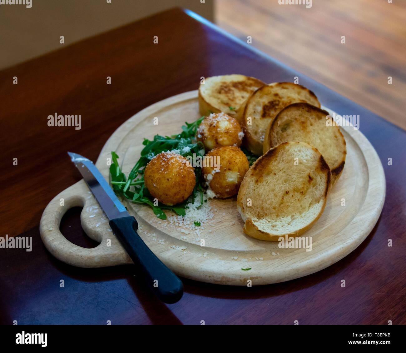 Uno snack costituito da toast fritti e formaggio di capra su un tavolo di legno, centrato, con spazio di copia Immagini Stock
