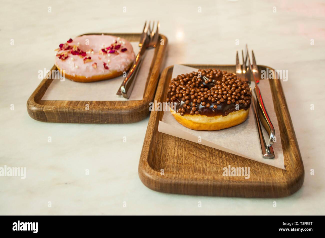 Delicicous ciambelle dolci su piastre di legno su un tavolo in un bar. Foto Stock