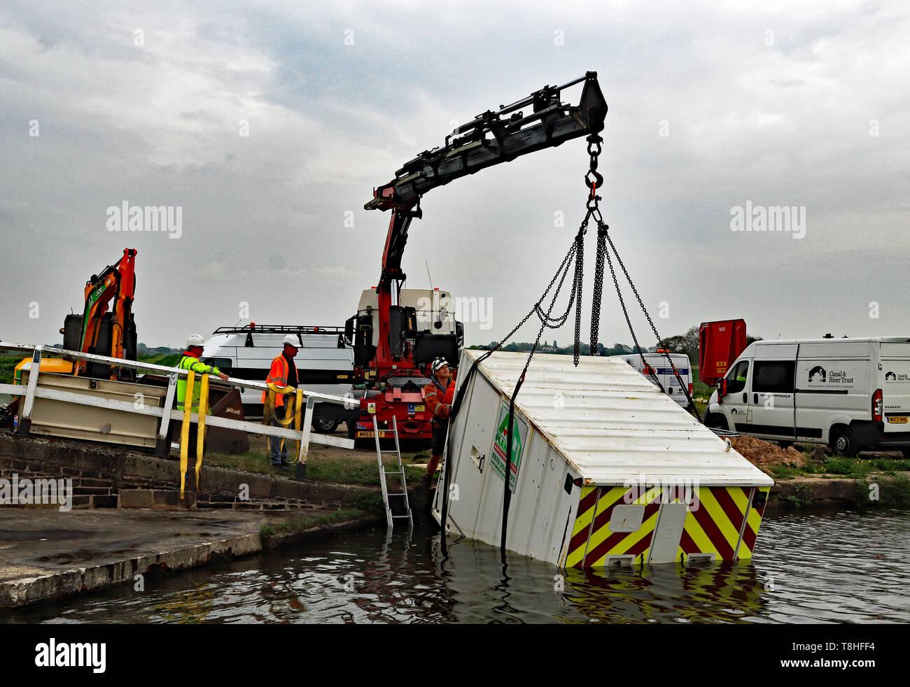Un contenitore di benessere viene sollevato fuori del Leeds e Liverpool canal vicino Haskayne a seguito di un atto di vandalismo con un JCB over night 23 Aprile 2019 Immagini Stock