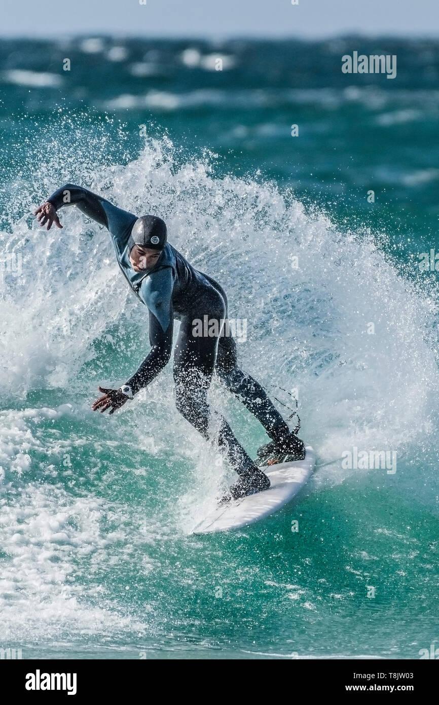 Un surfista compie un trucco a scatto su un'onda a Fistral a Newquay in Cornovaglia. Immagini Stock