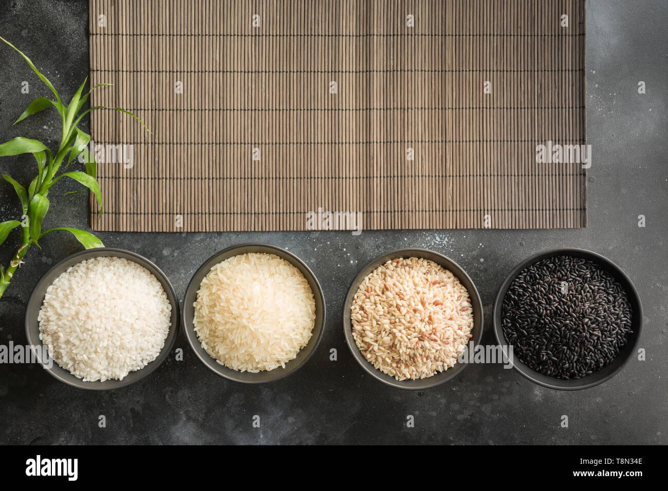 Diverse varietà di riso in ciotole. Vista dall'alto. Sfondo nero. Spazio per il testo. Immagini Stock