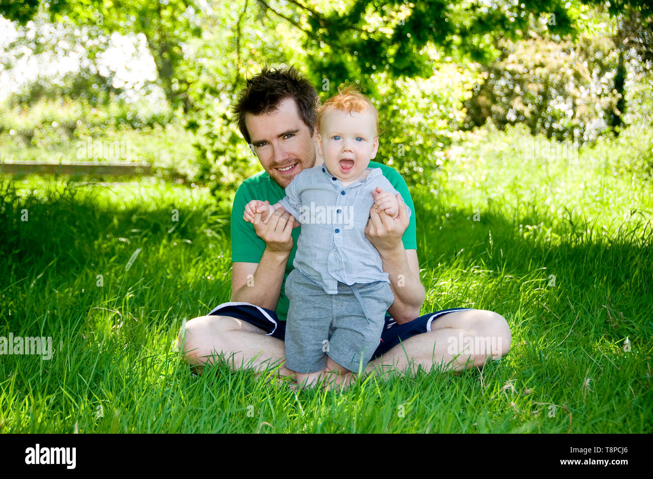 Giovani papà con bambino seduti all'aperto nel giardino in una giornata di sole. Immagini Stock