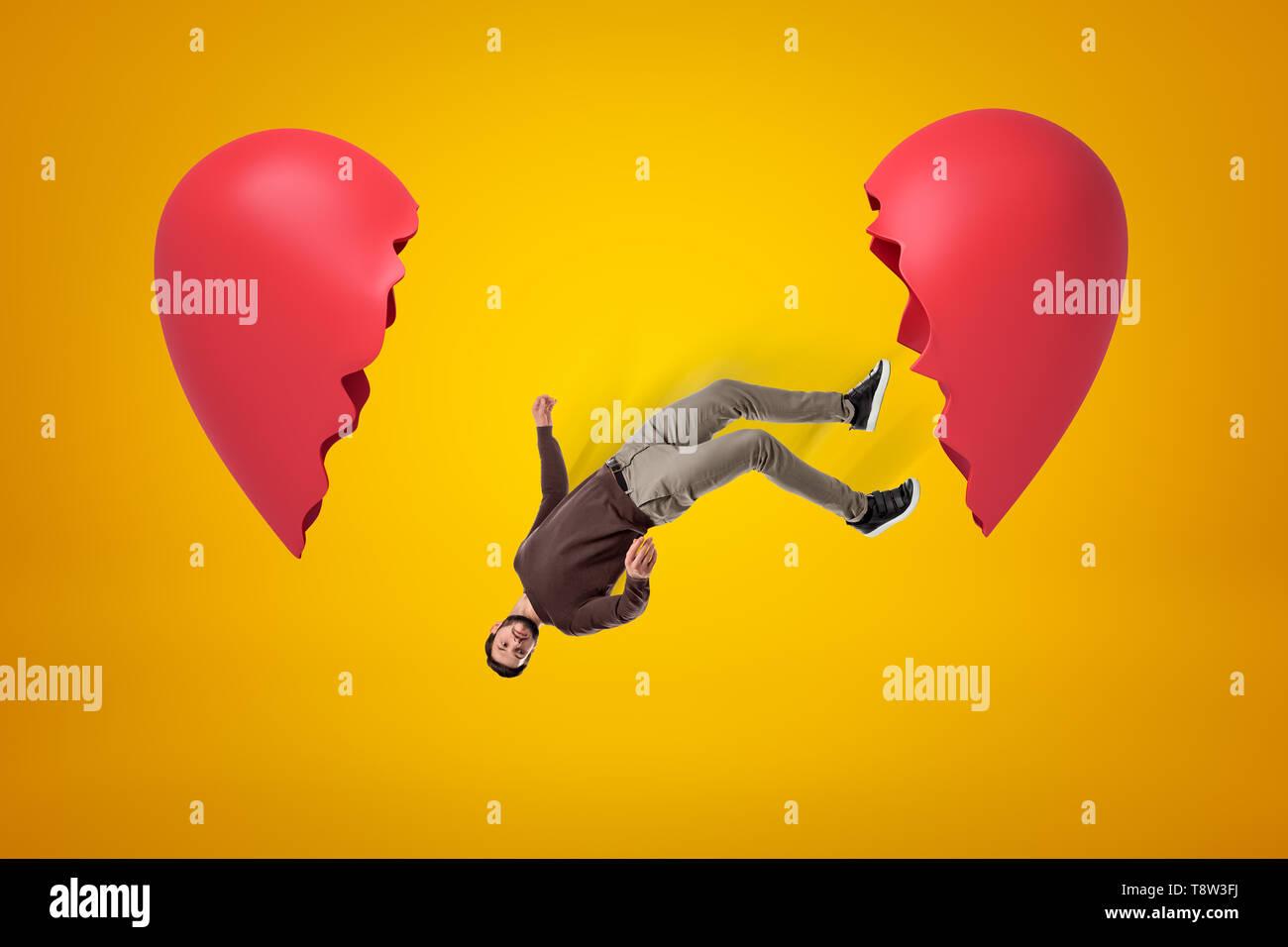 Giovane uomo in abiti casual cadere tra due cuore spezzato pezzi su sfondo giallo Immagini Stock