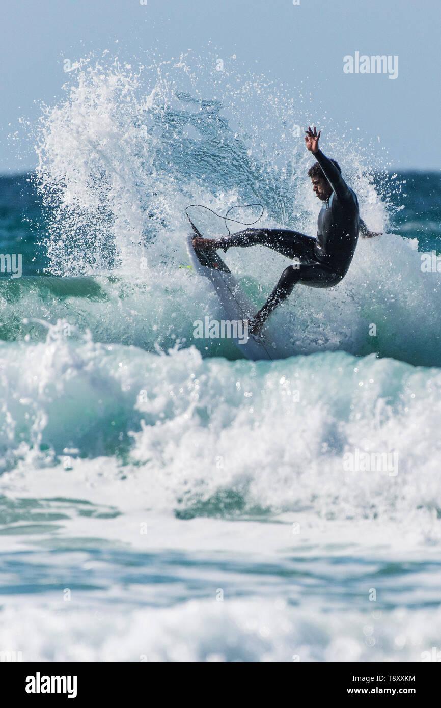 Drammatica azione di surf come un surfista esegue uno snap trick come cavalca un onda in un color giada mare a Fistral a Newquay in Cornovaglia. Immagini Stock
