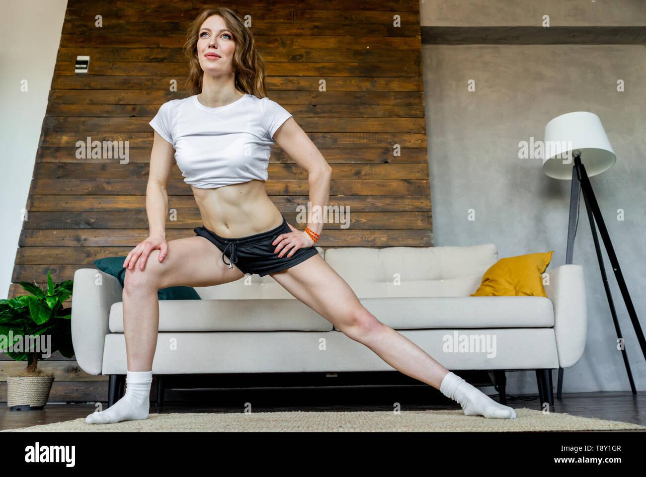 Giovane donna bionda facendo stretching esercizi yoga a casa. Uno stile di vita sano. Foto Stock