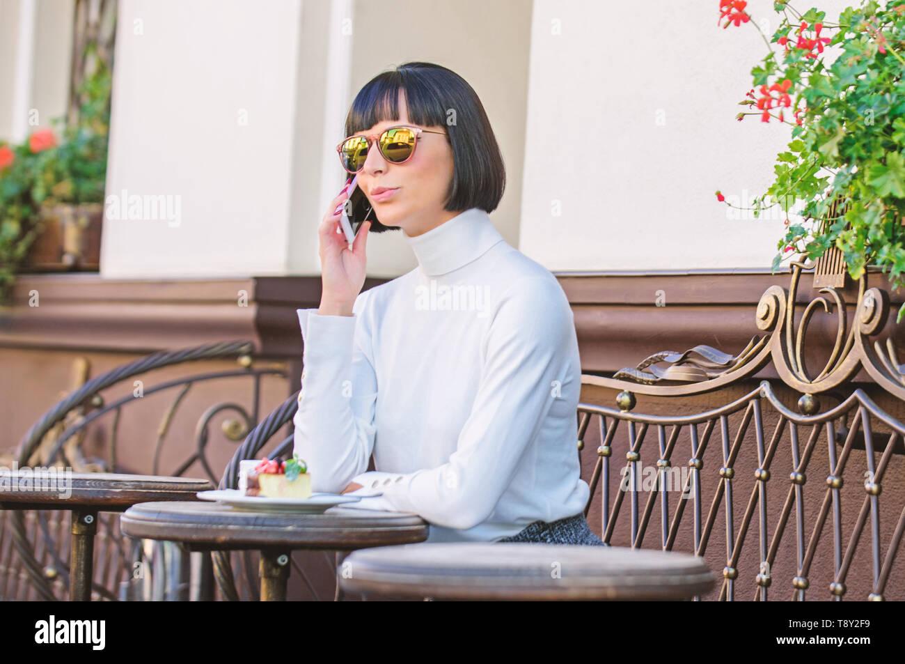 Chiamare amico. Ragazza signora alla moda con lo smartphone. Concetto di piacere. Donna elegante attraente brunette trascorrere tempo libero bar terrazza sfondo. Piacevole il tempo e il tempo libero. Relax e coffee break. Foto Stock
