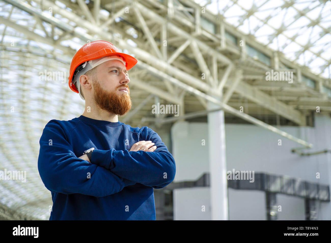 Il piano media ritratto di un uomo adulto in un casco attraversato le sue braccia, valuta, studi, guarda al lato orizzontale, libera spazio per la firma Immagini Stock