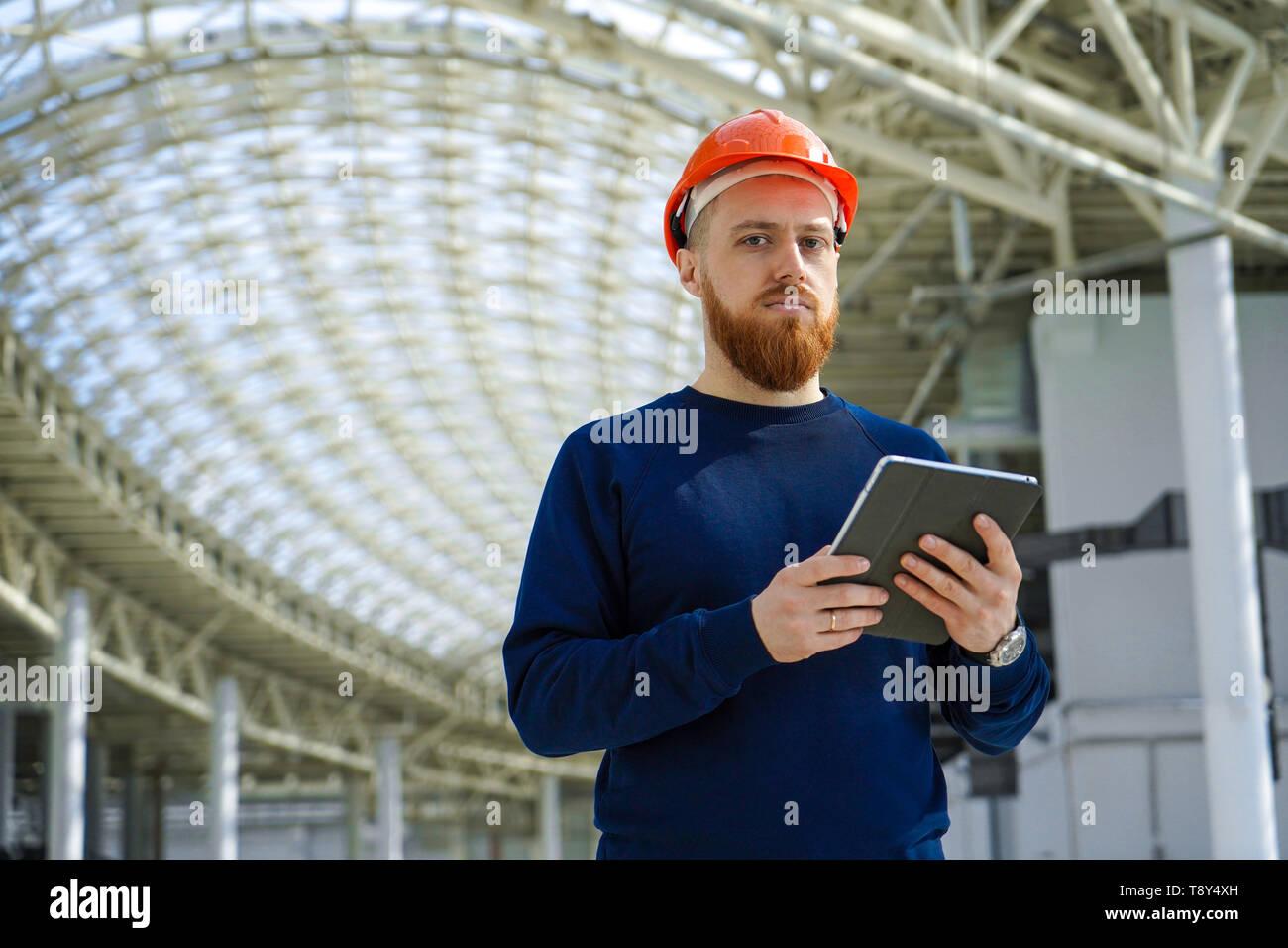 Il media plan è un ritratto di un uomo adulto in un casco di controllo o di controllo con la pianificazione, tenendo un tablet PC, orizzontale, spazio per la firma Immagini Stock