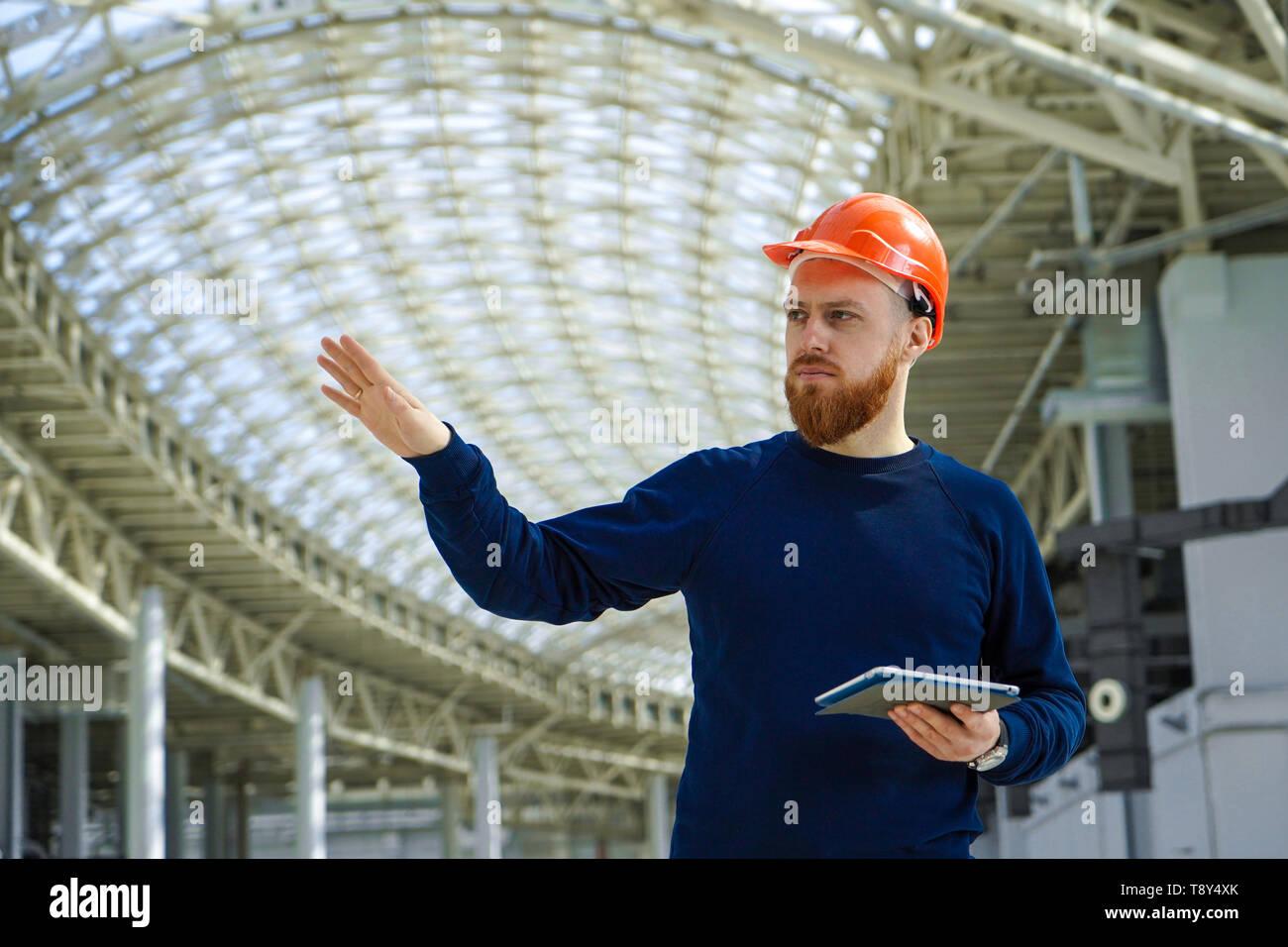 Il piano media ritratto di un uomo adulto in un casco parlando, mano rivolto di lato, tenendo in mano un tablet PC, orizzontale, spazio per la firma Immagini Stock
