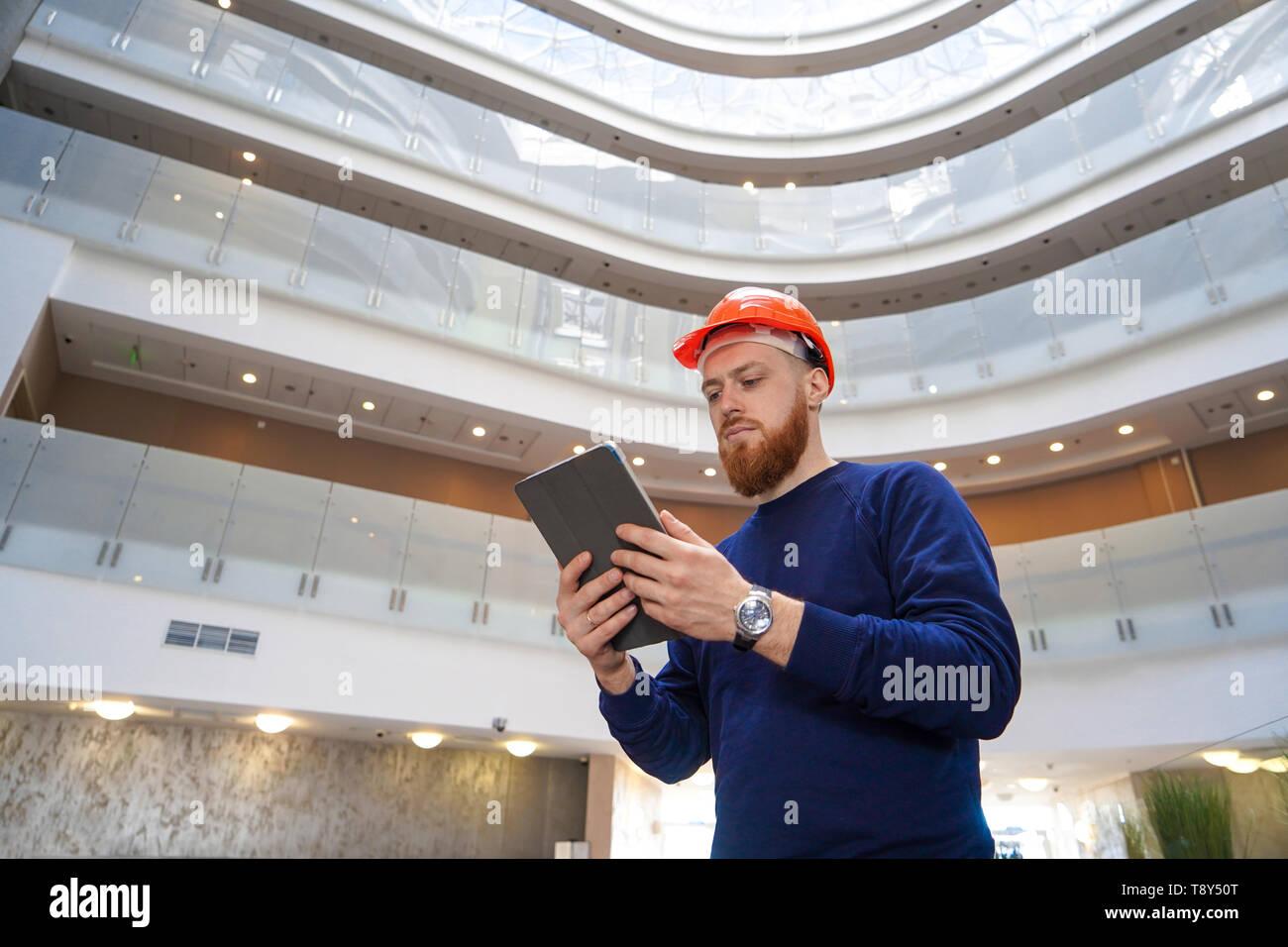 Il piano media ritratto di un uomo adulto in un casco guarda nel tablet personal computer, orizzontale, lo spazio per la firma libera Immagini Stock