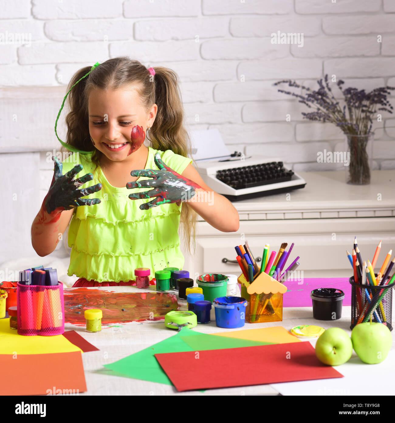 Pittore ragazza di verniciatura con vernici a tempera su tavola Immagini Stock