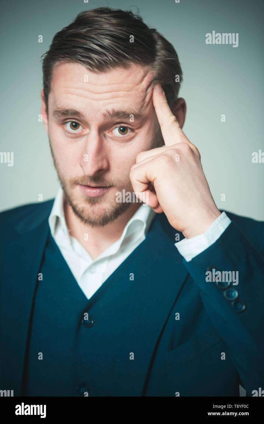 Persona pensosa. L'uomo calma grave alla ricerca concentrata mentre si tocca la testa cercando ricordare. Guy espressione tesa a ricordare le informazioni. Uomo Immagini Stock