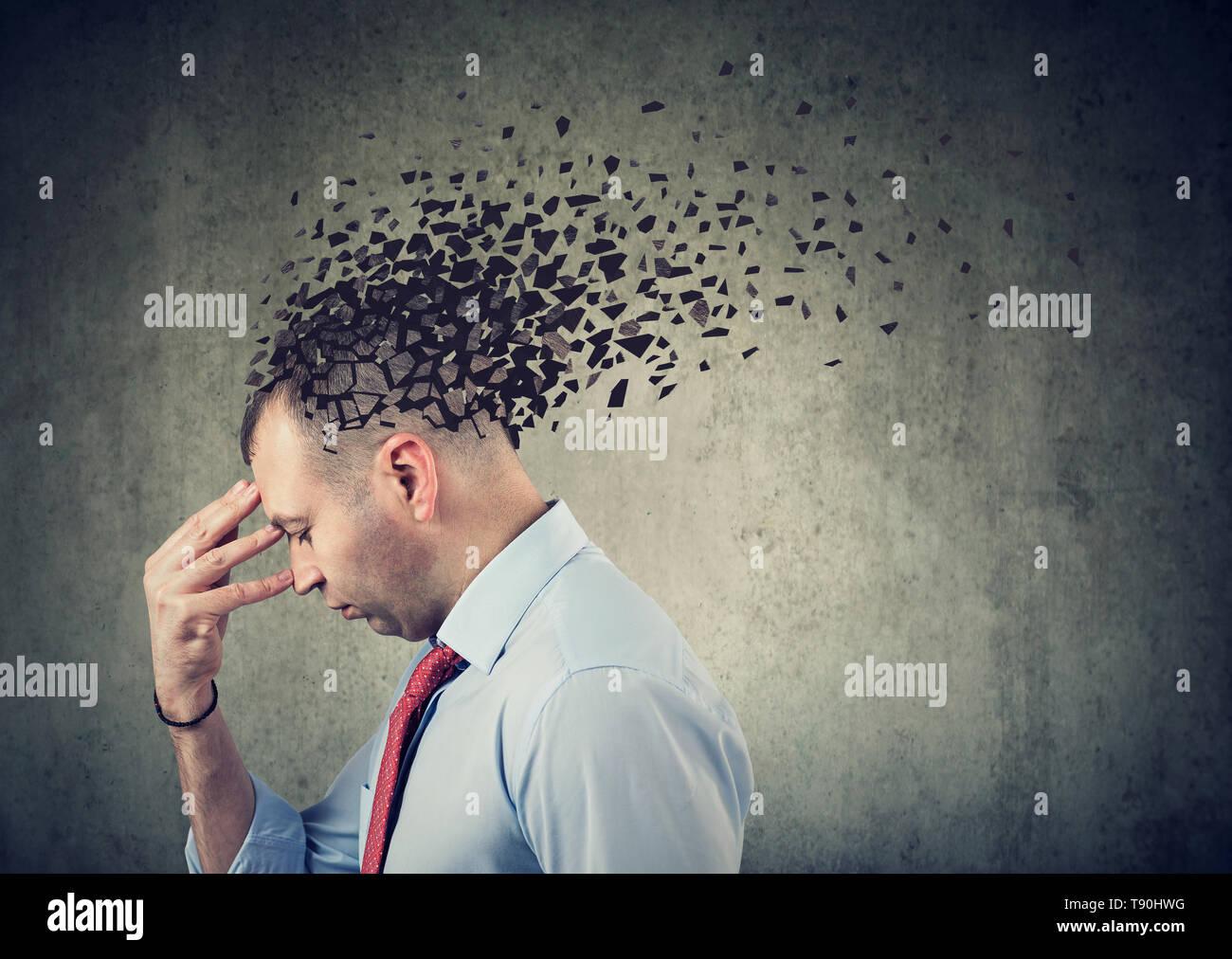 La perdita di memoria a causa di demenza o danni cerebrali. Profilo laterale di un uomo triste perdere parti di testa come simbolo della diminuita funzione della mente Foto Stock