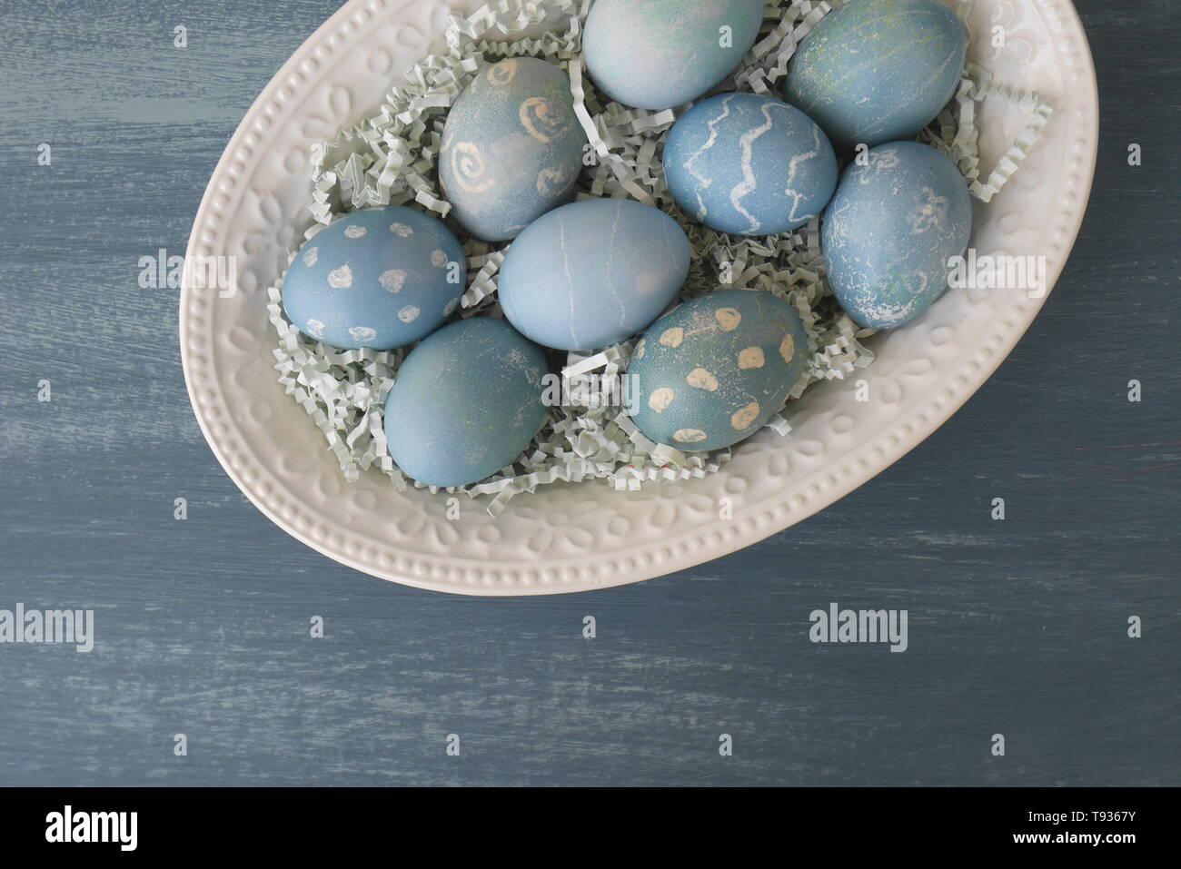 Dipinto di uova di Pasqua, colorato con un colorante dal cavolo rosso, in una ciotola su una chalk-verniciato blu legno invecchiato tavolo da cucina. Immagini Stock