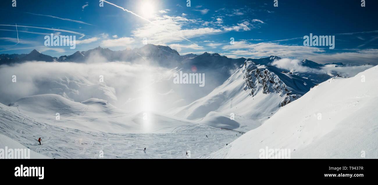 Vista panoramica verso il basso coperto di neve valle nella catena montuosa alpina con il gelo e la luce del sole sundog in aria sulla pista da sci Foto Stock