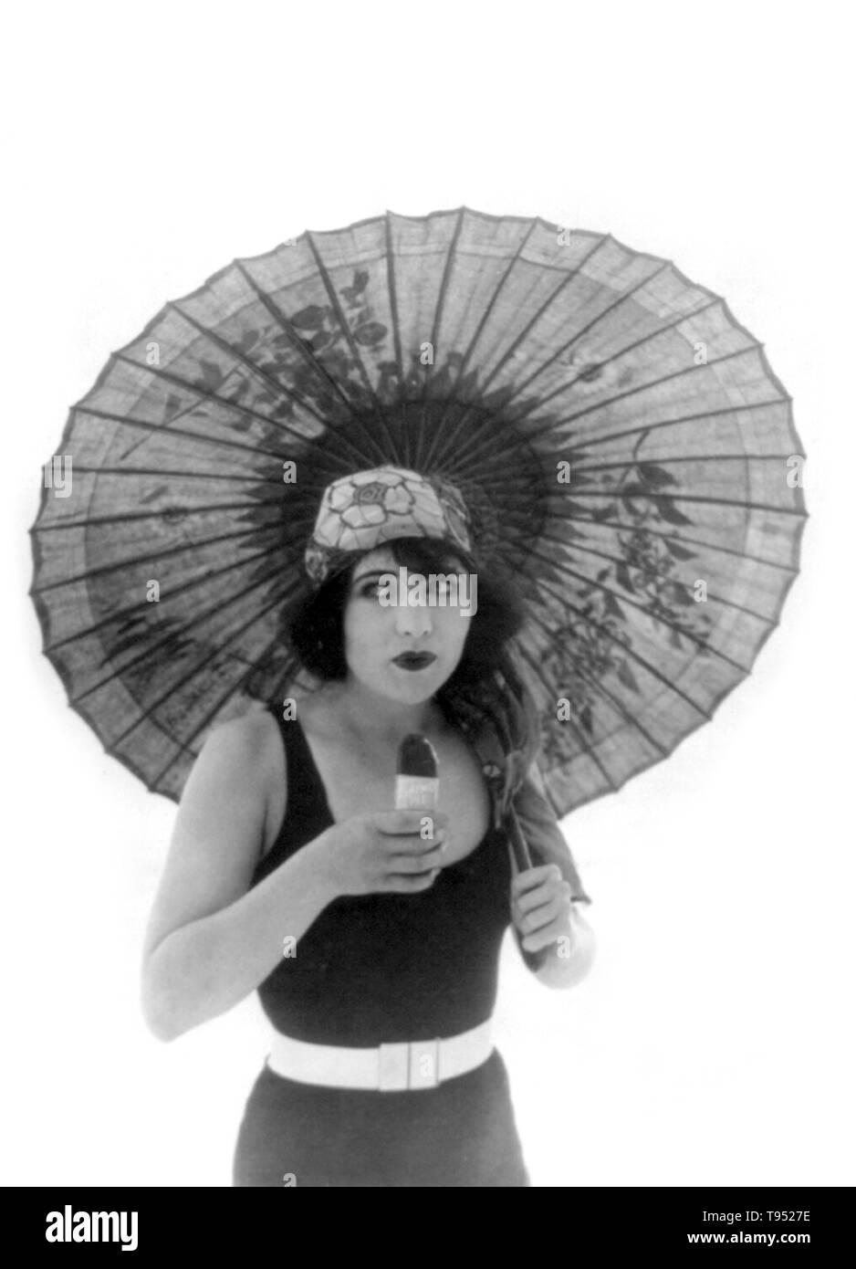 """Intitolato: """"Betty Compson con ombrellone, in costume da bagno, rivolta leggermente a destra, mangiare eschimese torta."""" Betty Compson (Marzo 19, 1897 - Aprile 18, 1974) è un actress americano e produttore di film. Più famosi in pellicole silenziose e inizio talkie, lei è il più noto nelle sue esibizioni nei Docks di New York e il Barker, quest'ultimo a guadagnare una nomination per il premio Oscar per la migliore attrice. La sua popolarità ha permesso di avere controllo creativo sul suo film come anche lei era in grado di produrre. Foto Stock"""