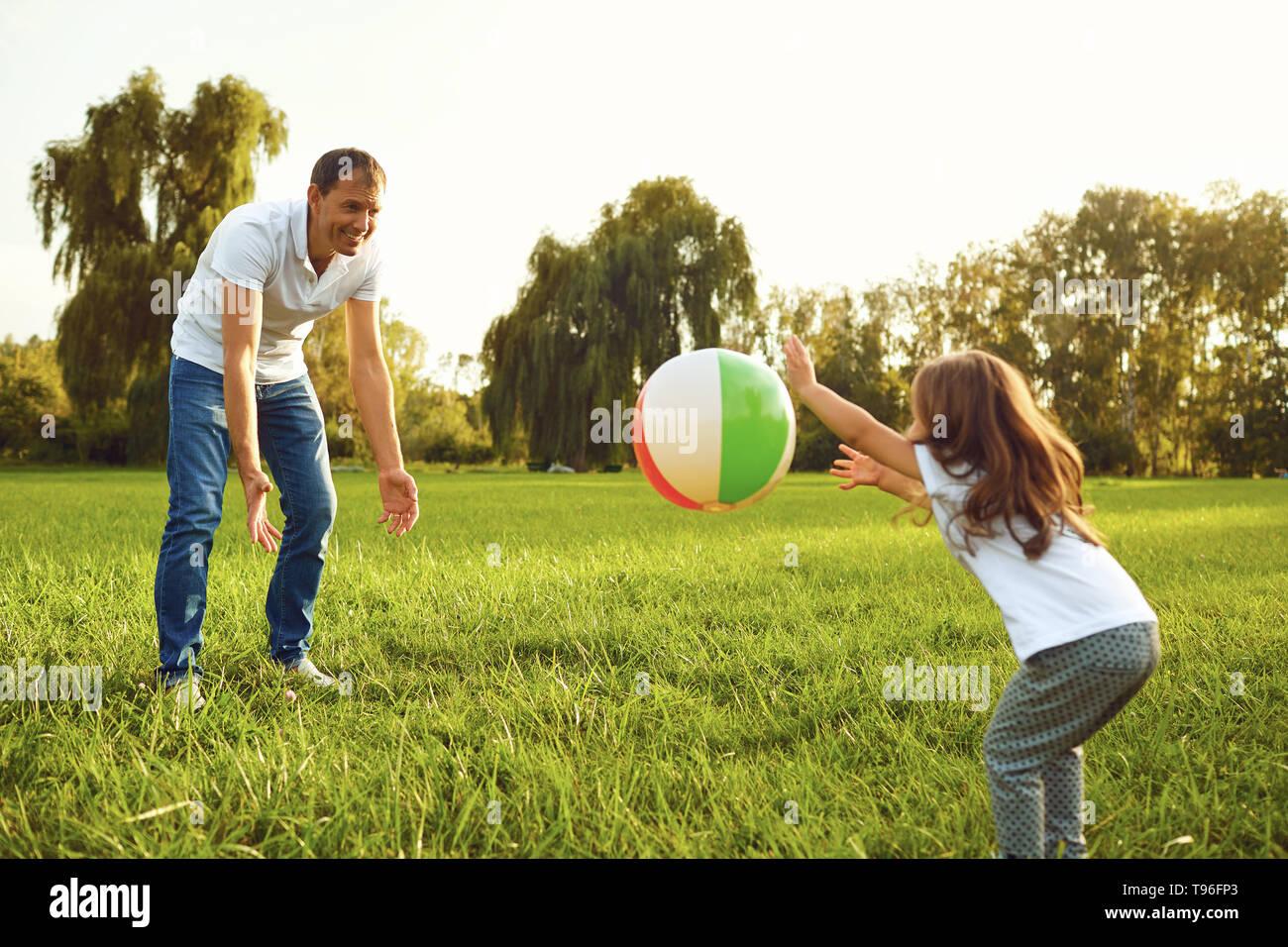 Padre con una piccola figlia di giocare con una palla in natura. Foto Stock