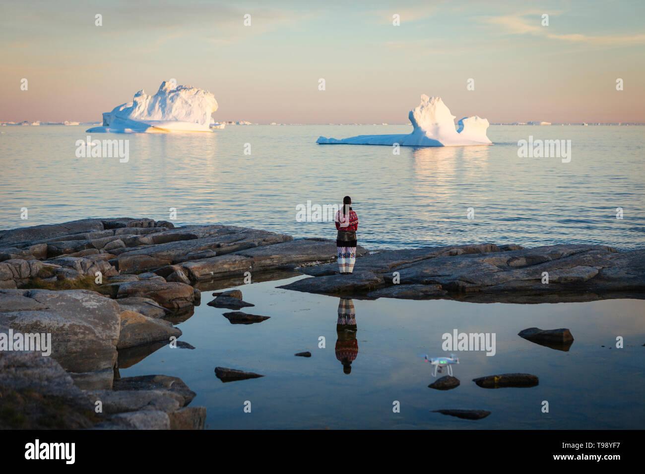 Inuit donna in abiti tradizionali sorge sulle rive della baia di Disko su Midsummer, Groenlandia Foto Stock