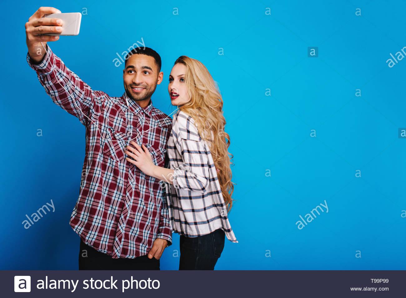 Elegante bello ragazzo rendendo selfie ritratto con attraente giovane donna con capelli lunghi biondi su sfondo blu. Divertimento e buon umore, rilassante, tempo libero, hobby. Posto per il testo Immagini Stock