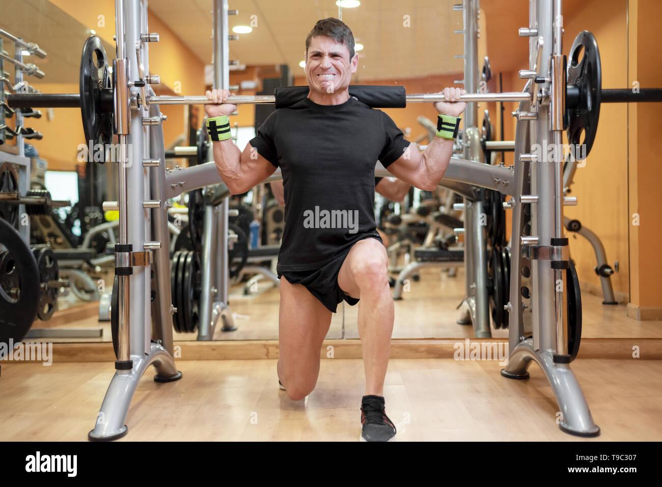 Sport, bodybuilding, lo stile di vita e il concetto di persone - giovane con barbell facendo squat in palestra . Immagini Stock