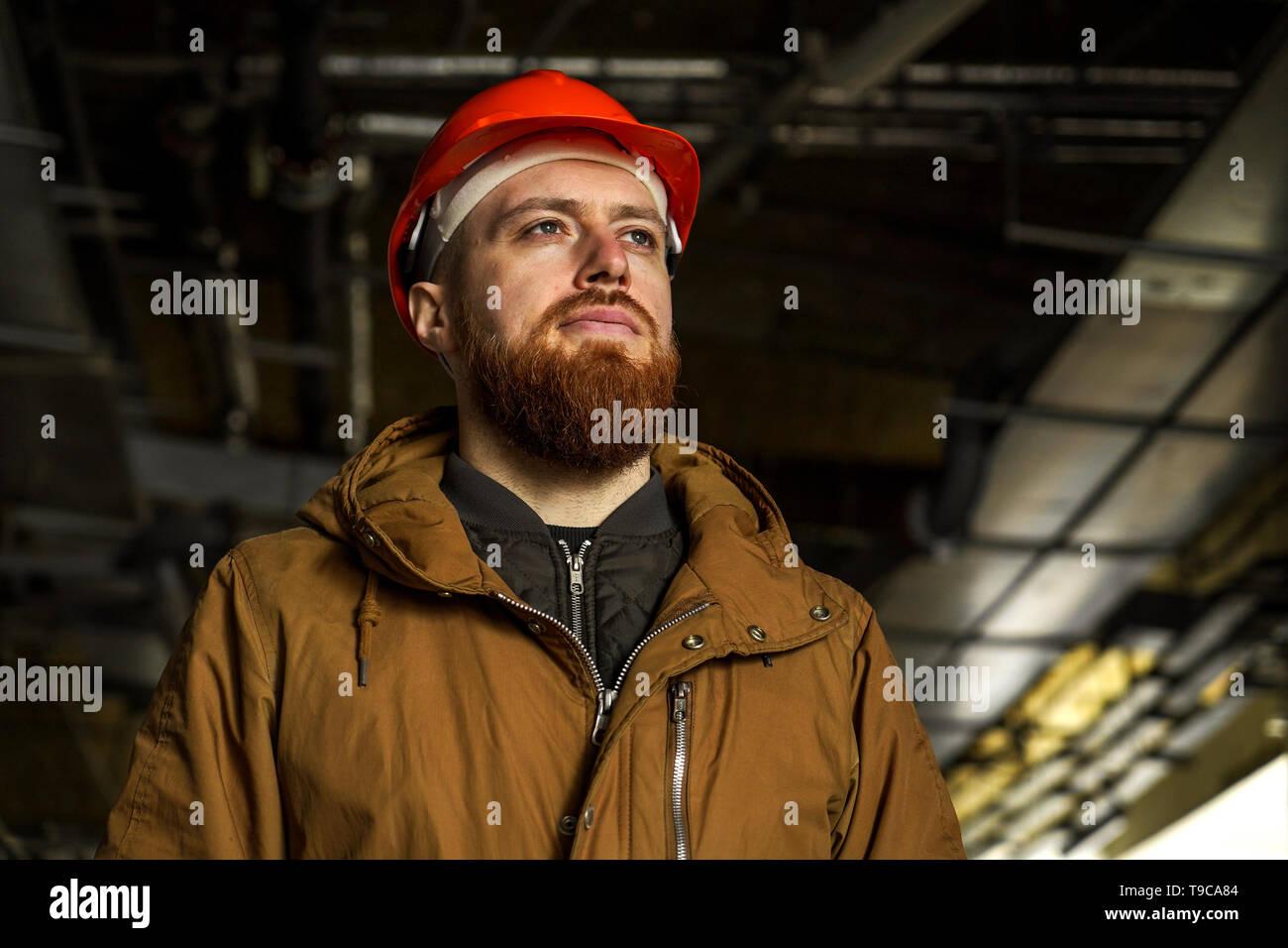 Il piano media ritratto di un uomo adulto in un casco con redhead, valuta, studi, guarda al lato orizzontale, libera spazio per la firma Immagini Stock