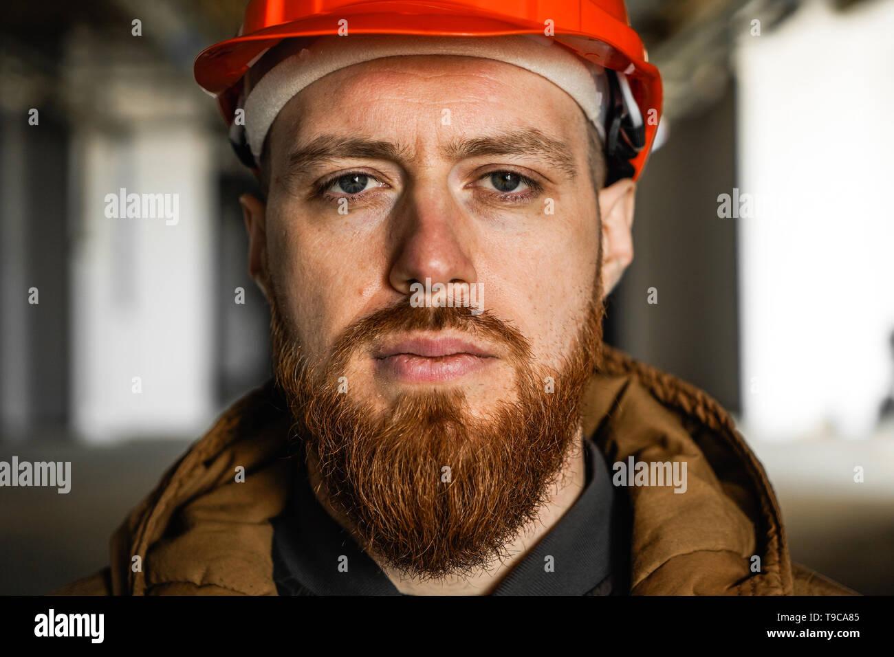 Il piano media ritratto di un uomo adulto in un casco con redhead, valuta, studi, guarda nel telaio, orizzontale, close up Immagini Stock