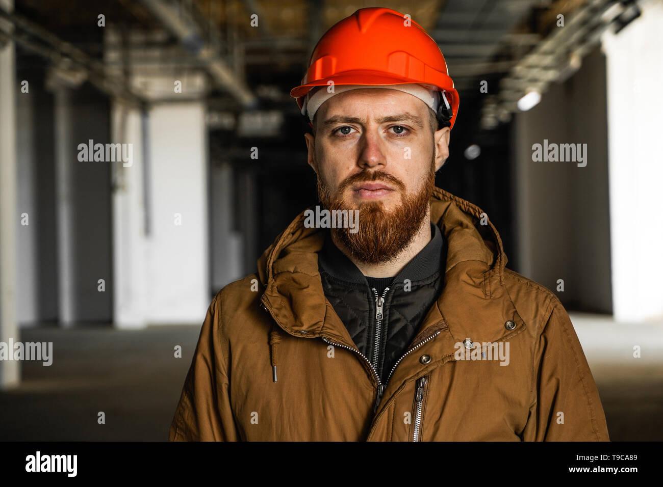 Il piano media ritratto di un uomo adulto in un casco con redhead, valuta, studi, guarda nel telaio, orizzontale dello spazio libero e la prospettiva Immagini Stock