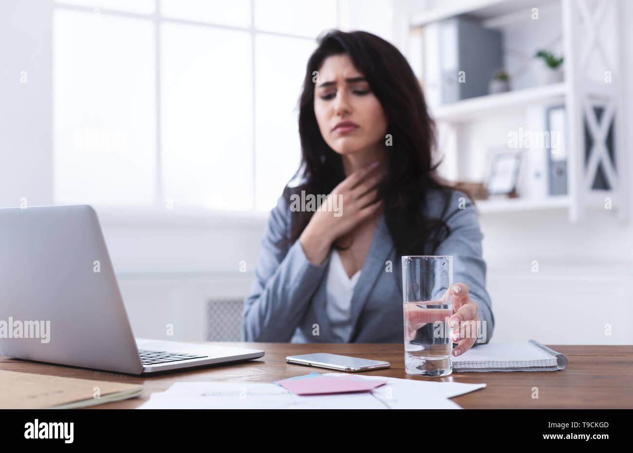 Malati imprenditrice con mal di gola cercando di lavorare Immagini Stock