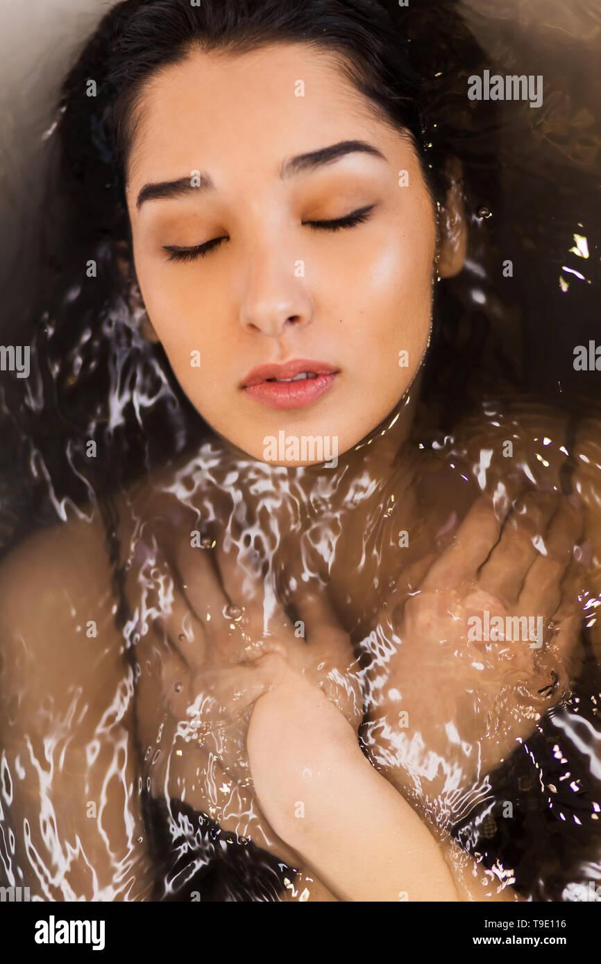 Close up ritratto di una giovane donna che sta con le braccia incrociate e gli occhi chiusi rilassante nell'acqua. Immagini Stock