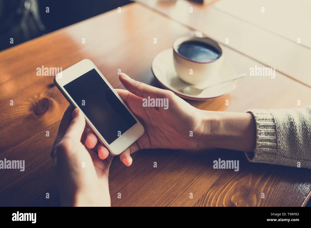 Donna che utilizza smartphone sul tavolo di legno al cafe'. Close-up immagine con reti sociali di concetto Foto Stock