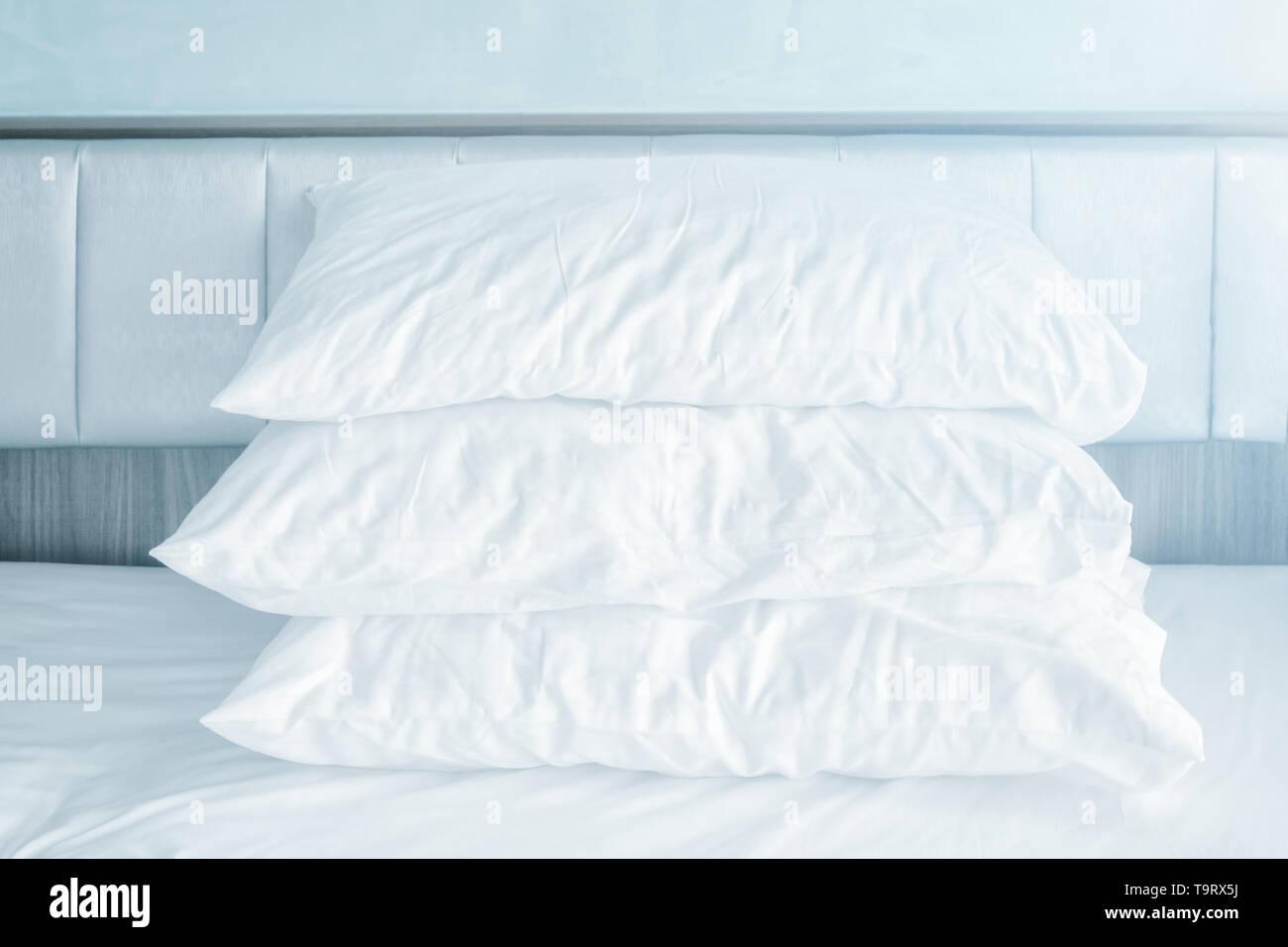 Comodi cuscini morbidi pila sulle bianche lenzuola nella moderna camera da letto Immagini Stock
