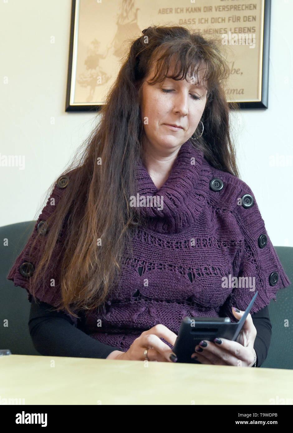 """Berlino, Germania. Il 17 maggio 2019. Viviane Czernietzki opera il suo smartphone al suo usato tavolino, che ella ha ricevuto constelessly provenienti da paesi vicini. La rete nebenan.de ha più di un milione di utenti in Germania, collega vicini gli uni con gli altri e invita il 24 maggio per la giornata dei vicini. (Per """"piattaforma online fornisce per i contatti non in linea tra vicini') Credito: Sven Braun/dpa/Alamy Live News Foto Stock"""