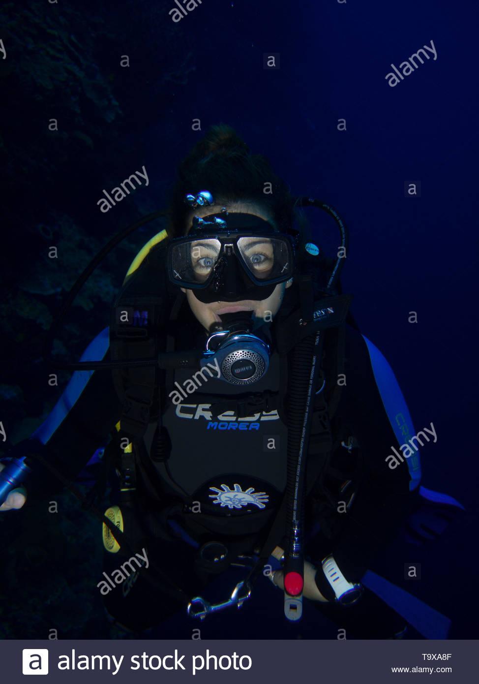 Donna scuba diver (esistente modello di rilascio) underwater godendo la barriera corallina del Parco Nazionale di Bunaken, Sulawesi, Indonesia Immagini Stock