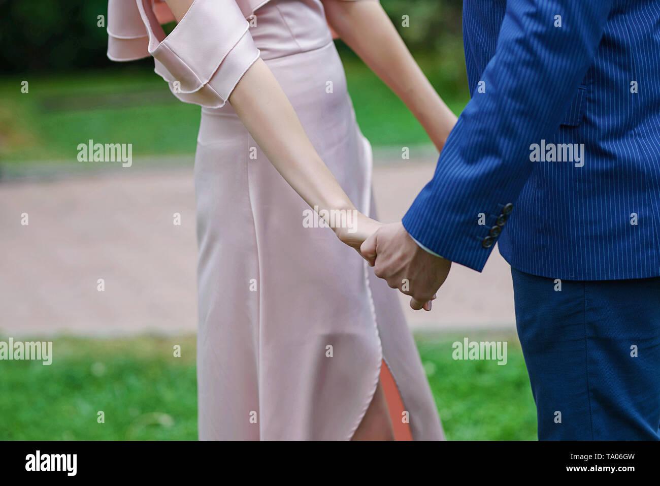Coppia caucasica, sposa in avorio Abito in raso e lo sposo in blu scuro tuta Holding Hands, con una offuscata, fuori fuoco sfondo Immagini Stock
