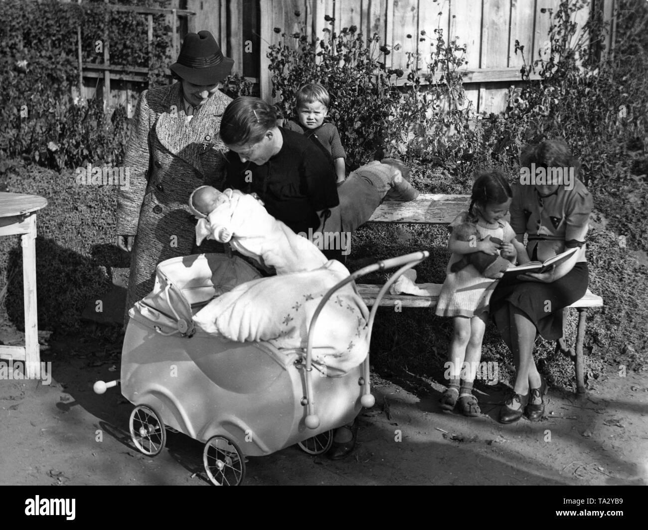 Il leader della NSF Kreisfrauenschaft (femminile di aiuto agenzia) visite evacuato famiglie prima la bomba di guerra. Qui, una madre sta mostrando il suo quinto bambino nato nella Prussia orientale. Foto Stock