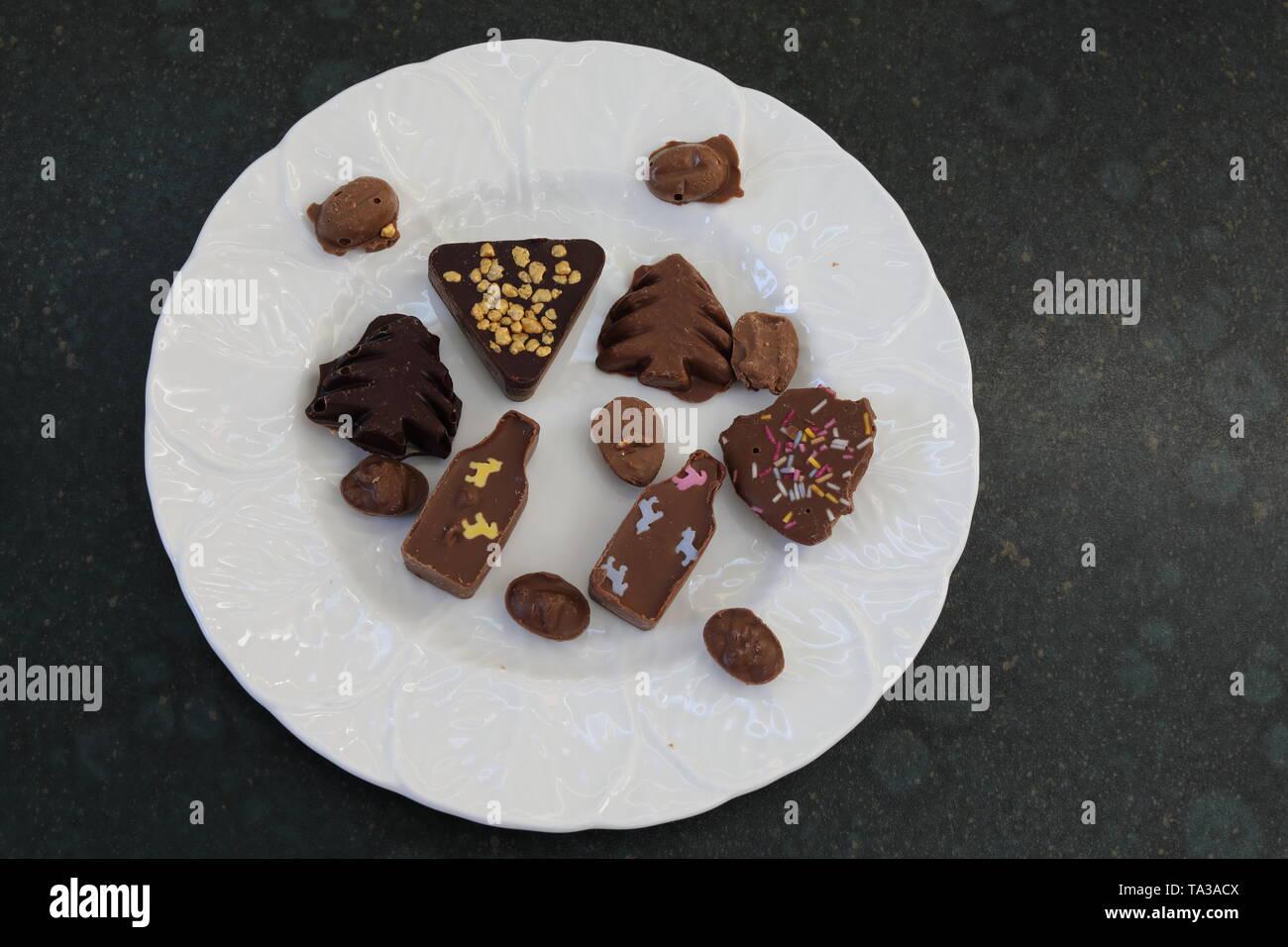 Una piastra bianca contenente una miscela di pezzetti di cioccolato in una varietà di forme Immagini Stock