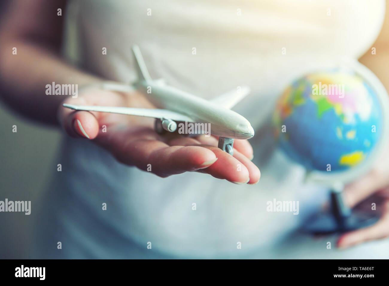 Donna femmina mani piccoli toy piano modello e mappa del globo. Il viaggio in aereo week-end di vacanza viaggio avventura biglietto di viaggio tour consegna aerea Foto Stock