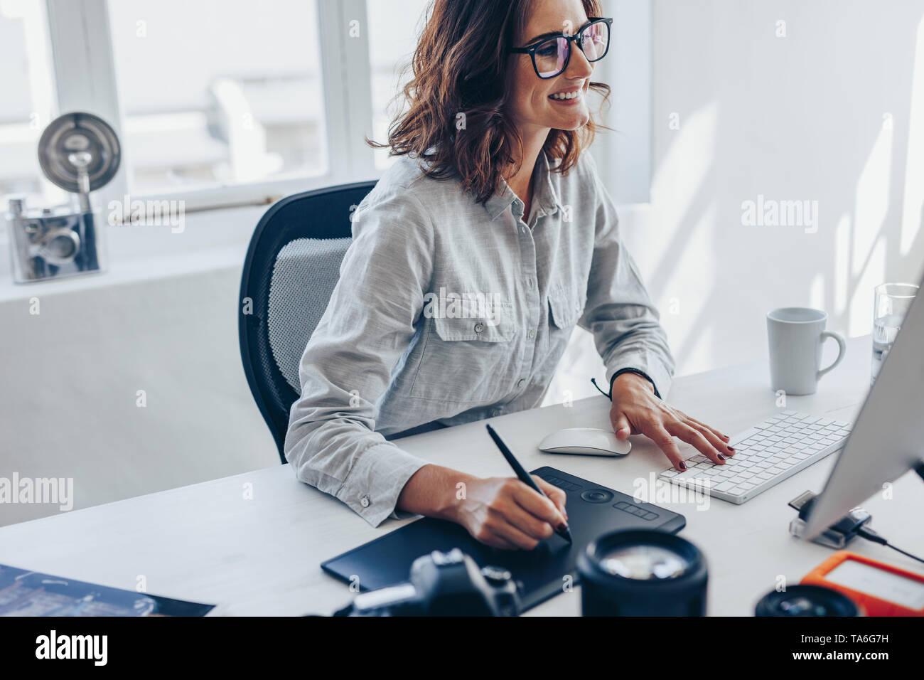 Femmina giovane fotografo lavorando sul computer utilizzando il tampone di disegno a scrivania in ufficio. Giovane donna caucasica tramite digital tavoletta grafica e disegno a penna Foto Stock