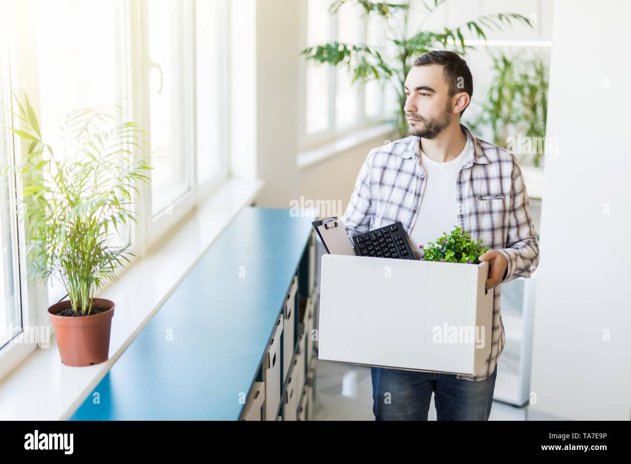 Business, la cottura e la perdita del posto di lavoro concetto - cotto - ufficio maschio lavoratore con box della sua roba personale e del suo triste colleghi Immagini Stock