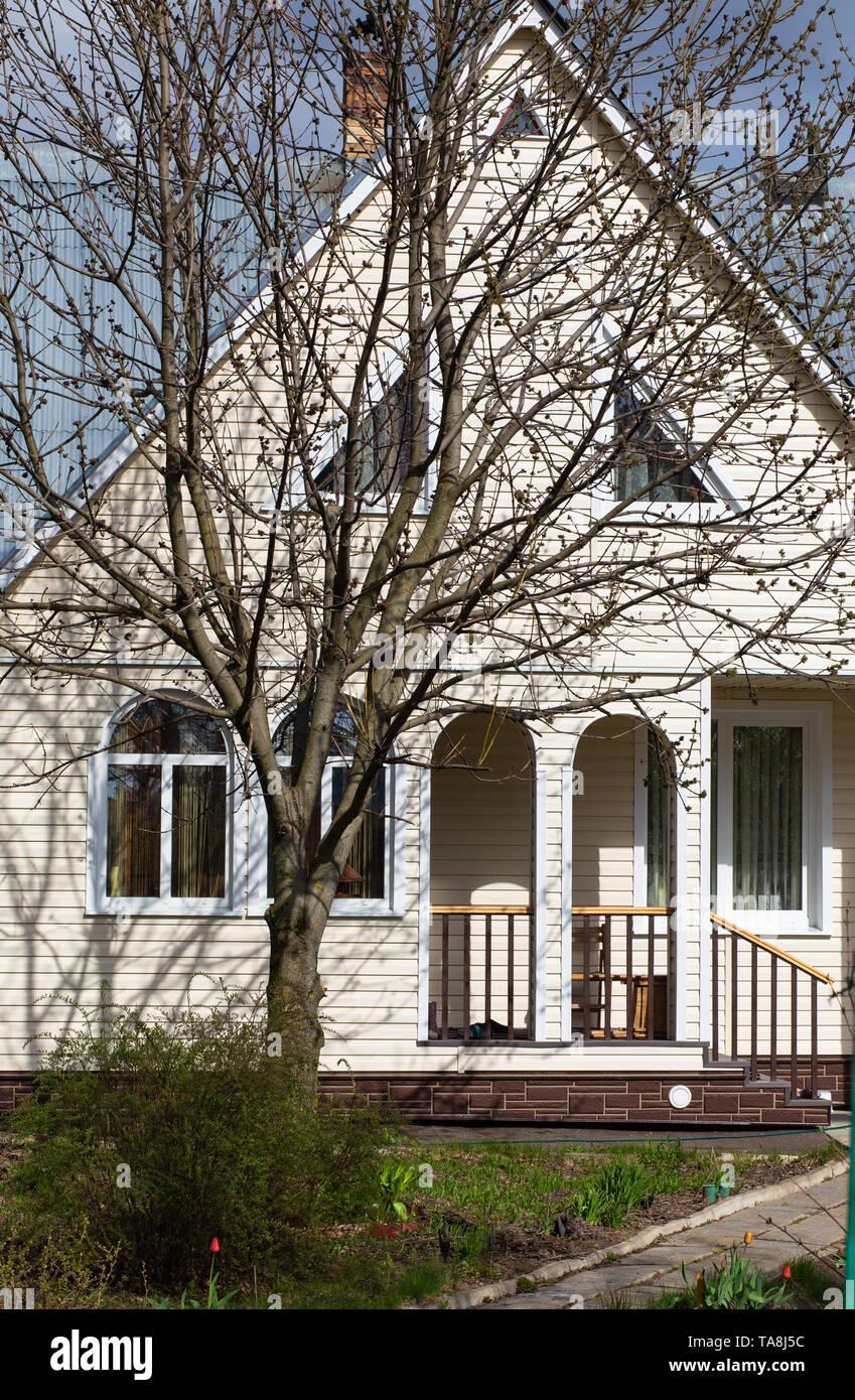 Facciata Casa Di Campagna la facciata di una casa di campagna e un grande albero senza