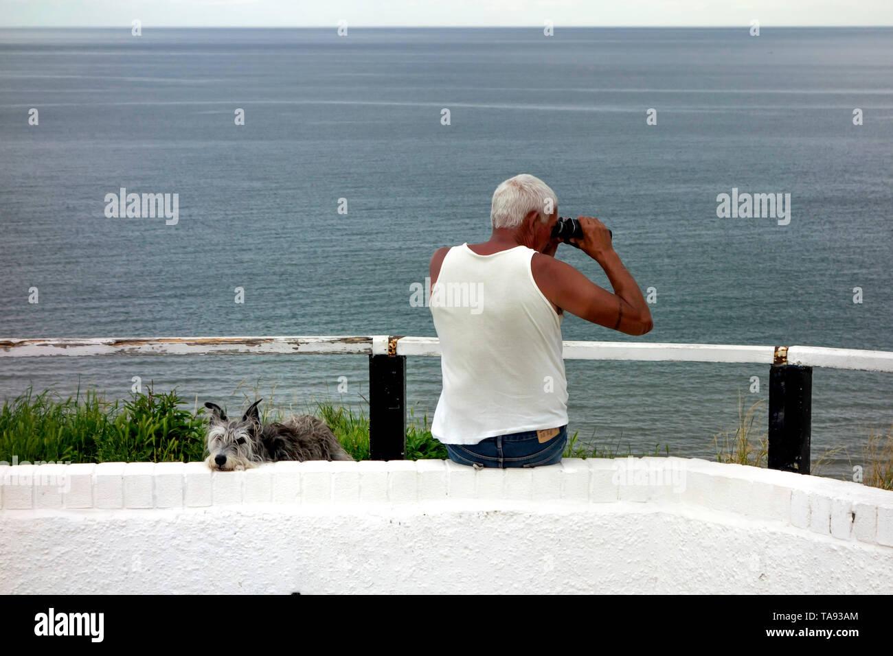 Ben costruito di mezza età uomo conciate indossando un singoletto e affacciata sul mare con un binocolo mentre il suo cane lurcher guarda a Saltburn North Yorkshire Immagini Stock