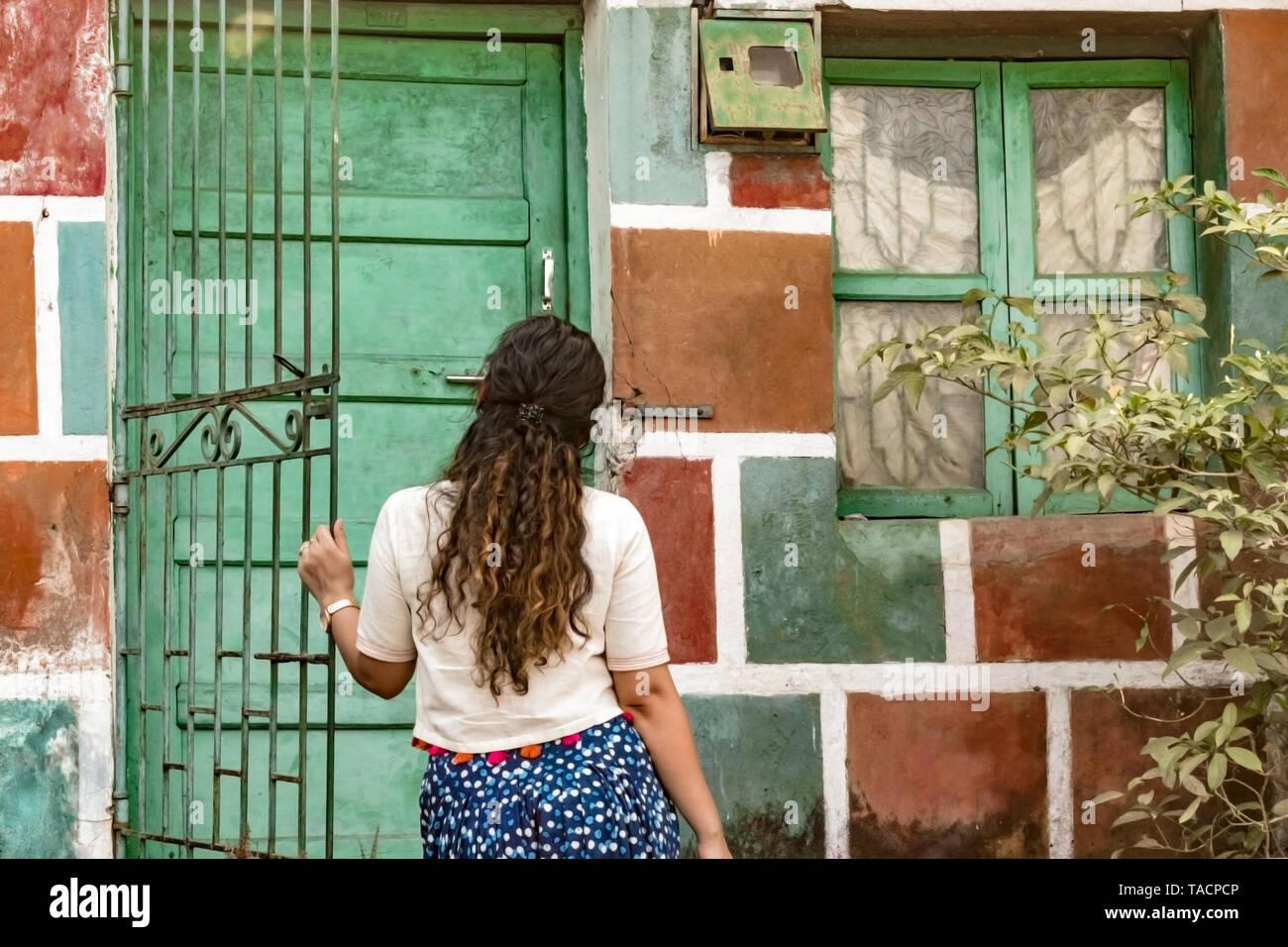 Vista posteriore di una ragazza con i capelli ricci, aprendo la porta di colorati dipinti casa indossando etnici Indiani, indossare un prodotto bianco superiore e blu salwaar patiala Immagini Stock