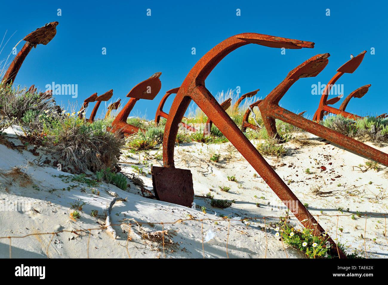 Decine di ancore giacenti in duna di sabbia in contrasto con il blu del cielo Immagini Stock