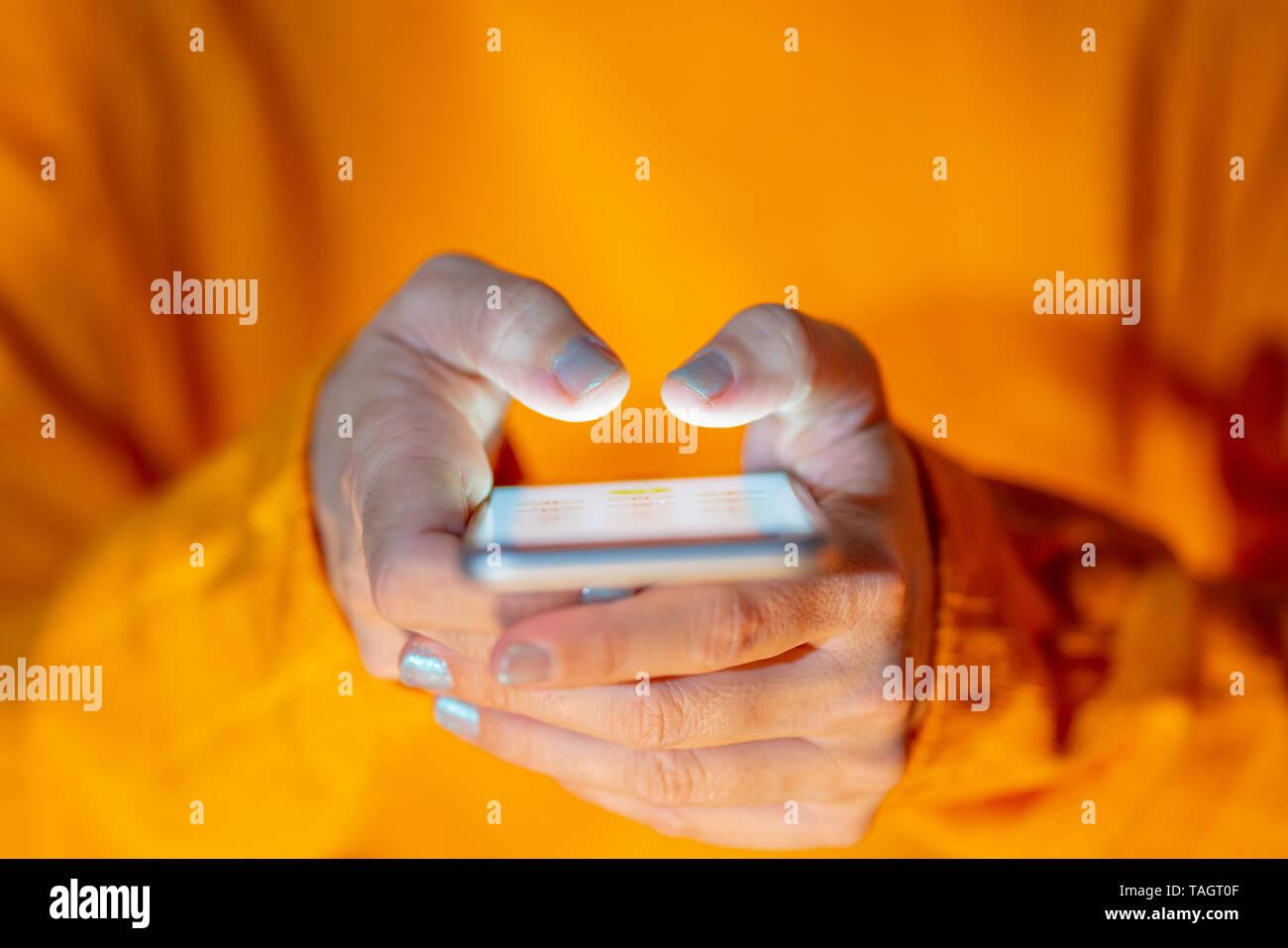 Le mani della donna giovane adolescente o invio di testo sui social media app in Internet e Mobile la dipendenza del fenomeno del cyber-bullismo Comunicazioni e tecnologia moderna Foto Stock
