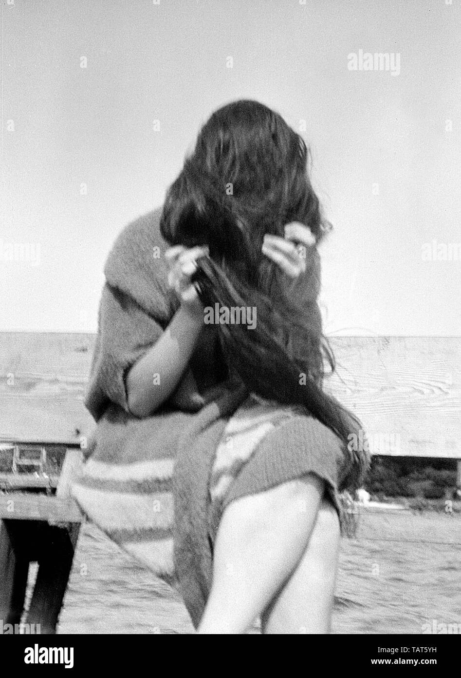 Una giovane donna nel periodo swimwear pone lungo la riva del lago Mendota a Madison, Wisconsin, ca. 1925. Foto Stock
