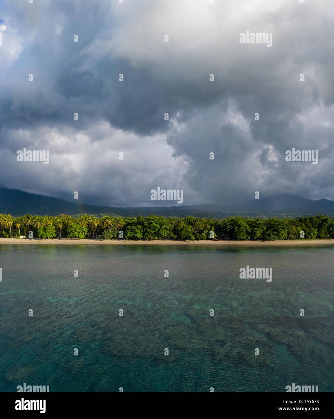 Pioggia nuvole deriva su SCENIC, costa tropicale di Flores, Indonesia. Questa grande isola è circondata da barriere coralline. Immagini Stock